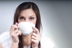 Mujer joven hermosa con la taza que bebe la bebida caliente Imagenes de archivo