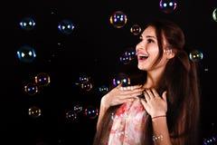 Mujer joven hermosa con las burbujas de jabón Foto de archivo
