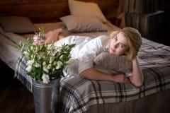 Mujer joven hermosa con las flores en la cama imagenes de archivo