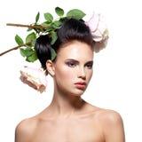 Mujer joven hermosa con las flores en pelo Fotos de archivo
