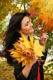 Mujer joven hermosa con las hojas de arce en parque del otoño Fotografía de archivo