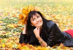 Mujer joven hermosa con las hojas de arce en parque del otoño Fotos de archivo libres de regalías