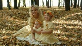 Mujer joven hermosa con las hojas de arce que se sientan con su bebé Foto de archivo libre de regalías