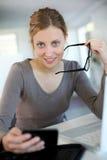Mujer joven hermosa con las lentes que estudia en casa Fotos de archivo libres de regalías
