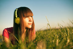 Mujer joven hermosa con los auriculares al aire libre Imagen de archivo