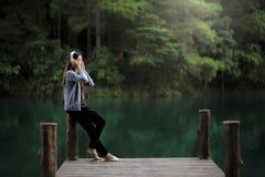 Mujer joven hermosa con los auriculares que se relajan en el muelle Imágenes de archivo libres de regalías