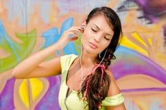 Mujer joven hermosa con los auriculares que se relajan y que escuchan la música. Imágenes de archivo libres de regalías