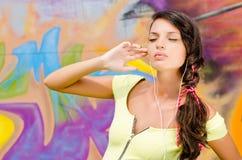 Mujer joven hermosa con los auriculares que se relajan y que escuchan la música. Fotos de archivo libres de regalías