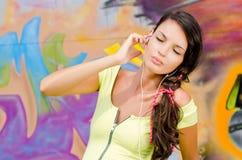 Mujer joven hermosa con los auriculares que se relajan y que escuchan la música. Imagenes de archivo