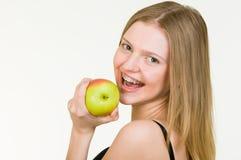Mujer joven hermosa con los corchetes que come la manzana Imagen de archivo