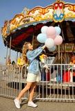 Mujer joven hermosa con los globos en el parque de atracciones foto de archivo