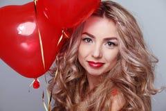 Mujer joven hermosa con los globos rojos del corazón Fotos de archivo