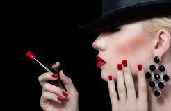 Mujer joven hermosa con los labios y la manicura rojos Imagen de archivo