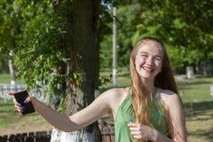 Mujer joven hermosa con los ojos azules en un fondo verde Mujer joven anhelante en una calle en un parque en el fondo fotografía de archivo libre de regalías