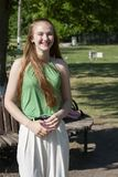 Mujer joven hermosa con los ojos azules en un fondo verde Mujer joven anhelante en una calle en un parque en el fondo foto de archivo