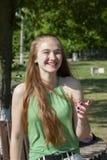 Mujer joven hermosa con los ojos azules en un fondo verde Mujer joven anhelante en una calle en un parque en el fondo imágenes de archivo libres de regalías