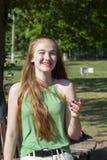 Mujer joven hermosa con los ojos azules en un fondo verde Mujer joven anhelante en una calle en un parque en el fondo fotos de archivo