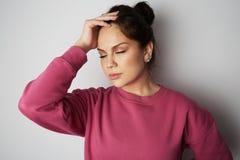 Mujer joven hermosa con los ojos cerrados que llevan sudadera con capucha rosada y que llevan a cabo la mano en la cabeza sobre f Imagen de archivo libre de regalías