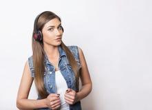 Mujer joven hermosa con los teléfonos principales Imagen de archivo libre de regalías