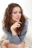 Mujer joven hermosa con los vidrios en la sentada gris Imagen de archivo