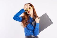 Mujer joven hermosa con los vidrios en un fondo ligero, profesor Foto de archivo libre de regalías
