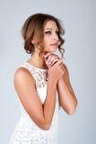 Mujer joven hermosa con maquillaje en el vestido blanco que presenta en gris Foto de archivo libre de regalías