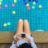 Mujer joven hermosa con noticias de lectura de la sonrisa hermosa buenas en el teléfono móvil que se sienta por el poolside imagenes de archivo