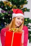 Mujer joven hermosa con oferta sonriente del sombrero de Papá Noel Foto de archivo libre de regalías
