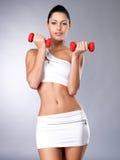 Mujer joven hermosa con pesas de gimnasia Fotos de archivo libres de regalías