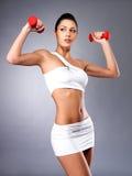 Mujer joven hermosa con pesas de gimnasia Imágenes de archivo libres de regalías