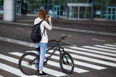 Mujer joven hermosa con smartphone y bicicleta en la calle Fotografía de archivo