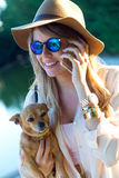 Mujer joven hermosa con su perro usando el teléfono móvil Fotografía de archivo