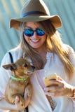 Mujer joven hermosa con su perro usando el teléfono móvil Imagen de archivo