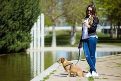 Mujer joven hermosa con su perro usando el teléfono móvil Fotografía de archivo libre de regalías