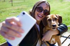 Mujer joven hermosa con su perro usando el teléfono móvil Imágenes de archivo libres de regalías