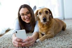 Mujer joven hermosa con su perro usando el teléfono móvil en casa Imagenes de archivo