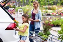 Mujer joven hermosa con sus plantas que llevan de la hija en el coche Fotos de archivo libres de regalías