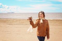 Mujer joven hermosa con un aeroplano del juguete en su mano en la orilla de la bahía en la ropa del piloto, espacio de la copia Imagenes de archivo