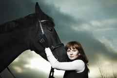 Mujer joven hermosa con un caballo negro Fotografía de archivo