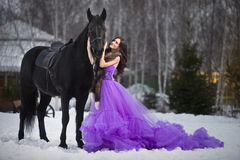 Mujer joven hermosa con un caballo negro Foto de archivo