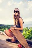 Mujer joven hermosa con un monopatín Foto de archivo libre de regalías