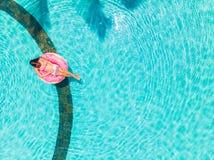 Mujer joven hermosa con un ordenador portátil rosado en un anillo inflable en el agua en la piscina el trabajar independientement fotografía de archivo
