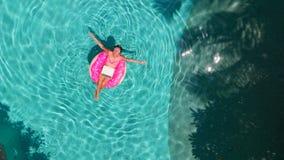 Mujer joven hermosa con un ordenador portátil rosado en un anillo inflable en el agua en la piscina el trabajar independientement foto de archivo libre de regalías