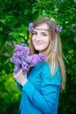 Mujer joven hermosa con un ramo de lilas en jardín de la primavera de las manos Fotografía de archivo libre de regalías