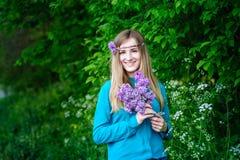Mujer joven hermosa con un ramo de lilas en jardín de la primavera de las manos Imagenes de archivo
