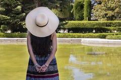 Mujer joven hermosa con un sombrero de paja, en el parque foto de archivo libre de regalías