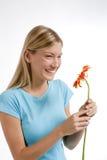 Mujer joven hermosa con una flor roja Foto de archivo