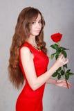 Mujer joven hermosa con una rosa roja Foto de archivo libre de regalías
