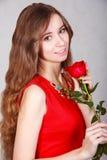 Mujer joven hermosa con una rosa roja Imágenes de archivo libres de regalías