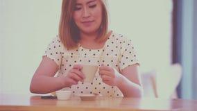 Mujer joven hermosa con una taza de café almacen de metraje de vídeo